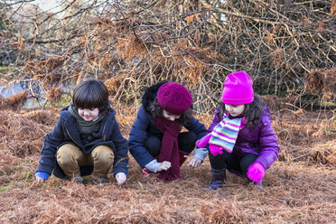 Three children crouching side by side in a park on a winter day - MGOF000052