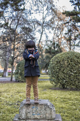 Little boy standing on a stone in a park on winter day - MGOF000061