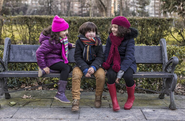 Three childrensitting on bench in a park on a winter day - MGOF000067