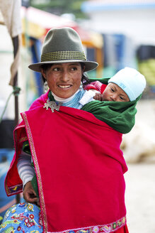 Ecuador, Young native woman with baby wearing red cape and hat - FP000020