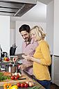 Couple cooking in kitchen using digital tablet - RBF002428