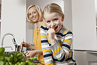 Mother with daughter eating carrot in kitchen - RBF002386