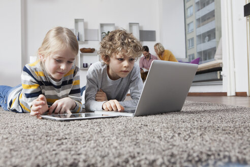 Brother and sister lying on floor using laptop and digital tablet - RBF002407