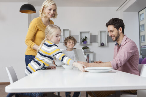 Family laying the table with father using laptop - RBF002410