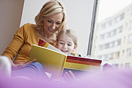 Mother reading picture book to daughter - RBF002415