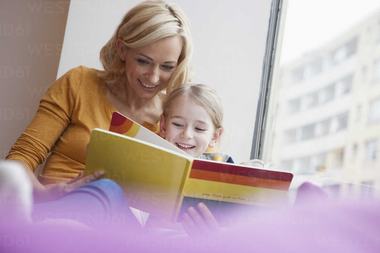 Mother reading picture book to daughter - RBF002415 - Rainer Berg/Westend61