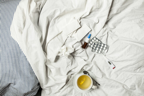 Lemon infusion, thermometer, pills, nasal spray and tissues in bed - SBDF001607