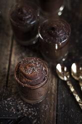 Glasses of vegan mousse au chocolat and tea spoons on wood - SBDF001598