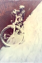 Snow covered bicycle leaning against wall - DWIF000430