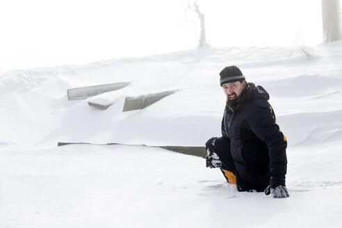 Germany, Baden-Wuerttemberg, Waldshut-Tiengen, man sinking in deep snow - MIDF000048