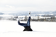 Germany, Baden-Wuerttemberg, Waldshut-Tiengen, playful woman in snow doing a headstand - MIDF000050