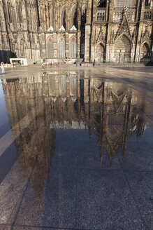 Germany, Cologne, Cologne Cathedral reflecting in a puddle - WIF001385