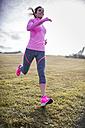 Spain, Gijon, sportive young woman running on meadow - MGOF000084