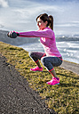 Spain, Gijon, sportive young woman doing workouts at the coast - MGOF000092