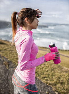Spain, Gijon, sportive young woman with water bottle at the coast - MGOF000095