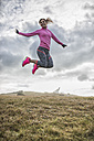 Spain, Gijon, sportive young woman jumping on meadow - MGOF000103
