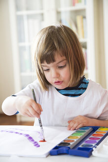 Portrait of smiling little girl painting with watercolours - LVF002796