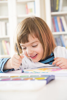 Portrait of smiling little girl painting with watercolours - LVF002804