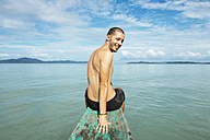 Philippines, Palawan, El Nido, man sitting on the bow of a boat - GEMF000033