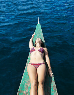 Philippines, Palawan, El Nido, sunbathing woman lying on the bow of a boat - GEMF000038