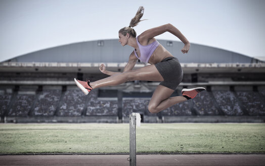 Athlete jumping over hurdle - ZEF007478