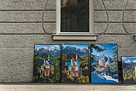Germany, Schwangau, posters of Neuschwanstein Castle leaning at house front - TC004535