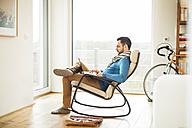 Young man sitting on rocking chair using laptop - UUF003337
