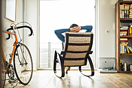 Man sitting on rocking chair looking out of window - UUF003344