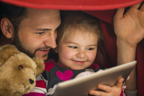 Father and daughter with digital tablet under blanket - UUF003357