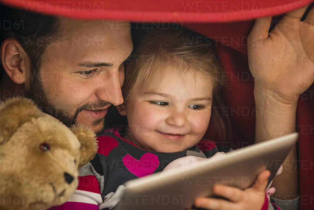 Father and daughter with digital tablet under blanket - UUF003357 - Uwe Umstätter/Westend61