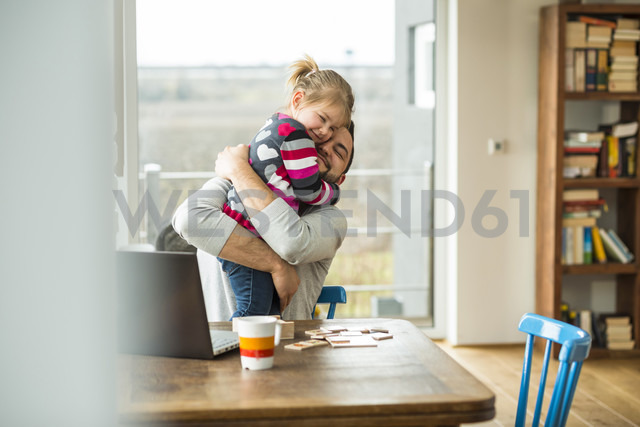 Father and daughter hugging at wooden table - UUF003400 - Uwe Umstätter/Westend61