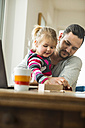 Father and daughter playing a game at wooden table - UUF003367
