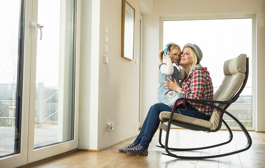 Mother and daughter on rocking chair sharing headphones - UUF003379