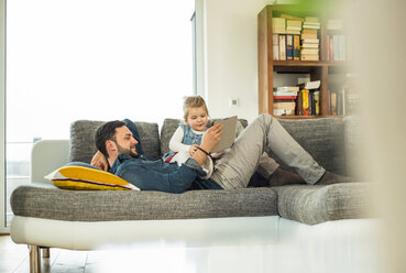 Father and daughter with digital tablet on sofa - UUF003390