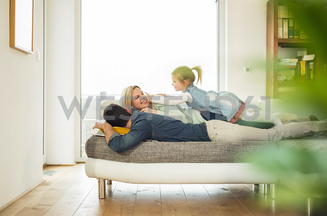Family lying on couch on top of each other - UUF003391