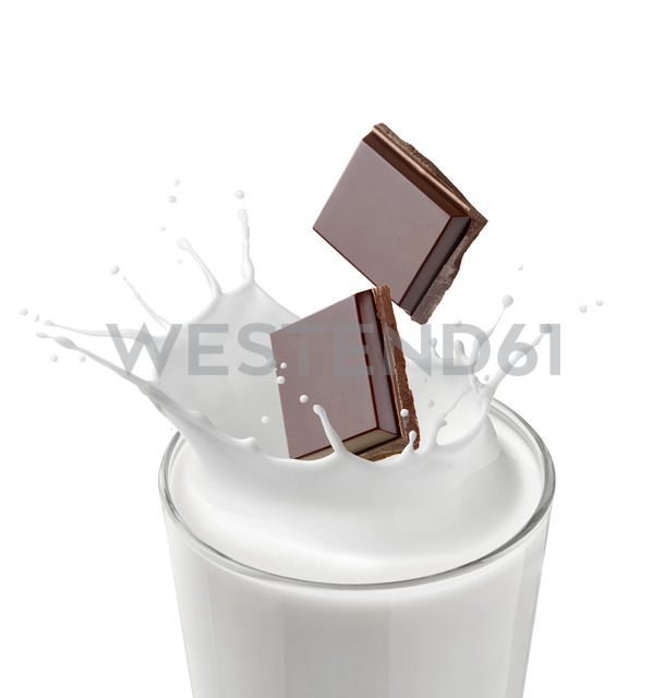 Two pieces of chocolate falling in glass of milk in front of white background - RAMF000044