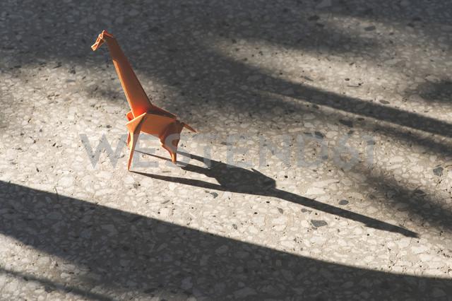Orange origami giraffe on stone floor - DEGF000126