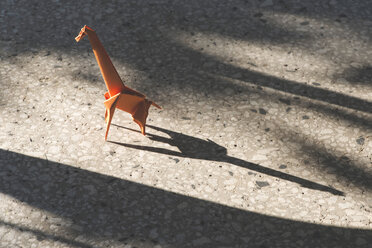 Orange origami giraffe on stone floor - DEGF000126
