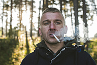 Bulgaria, man smoking cigarette in the forest - DEGF000219