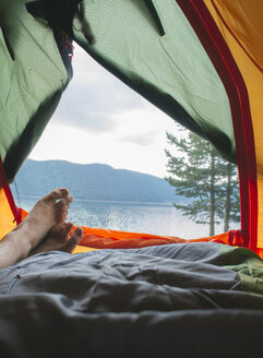 Bulgaria, man's leg in a tent with view to water - DEGF000223