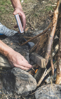 Man's hands lighting a fire on a meadow - DEGF000230