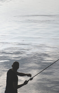 Silhouette of man fishing at dam - DEGF000235