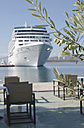 Greece, olive twig with cruise liner moored at harbour in the background - DEGF000147