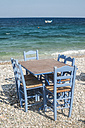 Greece, table and chairs of taverna at seashore - DEGF000246
