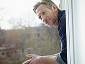 Germany, Cologne, Mature man looking out of window - RHF000494