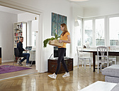 Mature man working from home, adult daughter carrying box with vegetables - RHF000500