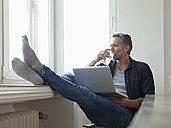 Germany, Cologne, Mature man sitting at window using laptop, feet up - RHF000512