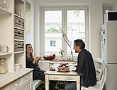 Young woman and mature man sitting in kitchen, having breakfast - RHF000548