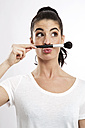 Portrait of young woman with make-up-brush pouting mouth - GDF000664