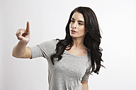 Portrait of young woman pointing in the air - GDF000669
